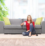 Woman drinking coffee seated by a sofa. At home shot with tilt and shift lens Stock Photography
