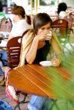 Woman drinking at a coffee shop. Woman drinking coffee at a table outside shop Royalty Free Stock Images