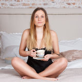 Woman drinking a coffee sitting on bed at home Royalty Free Stock Photography