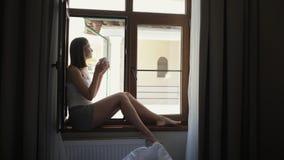 Woman is drinking coffee sitting on windowsill. Near open window stock video footage