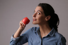 Woman Drinking Coffee from Small Red Cup Stock Photography