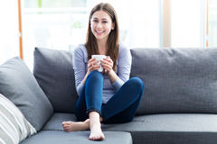 Woman drinking coffee on sofa Stock Photography
