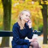 Woman drinking coffee and speaking on the phone in the Luxembourg garden of Paris on a fall day. Beautiful young woman drinking coffee and speaking on the phone royalty free stock photos