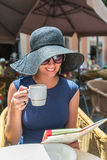 Woman drinking coffee at street cafe and looking on map Stock Image