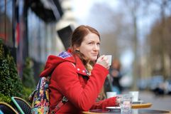 Woman drinking coffee in a street cafe Royalty Free Stock Photos