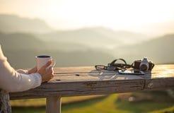 Woman drinking coffee in sun sitting outdoor in sunshine light enjoying her morning coffee, Stock Photos