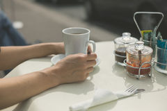 Woman drinking coffee at table outside Stock Image