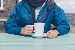Woman drinking coffee at table outside Stock Photography