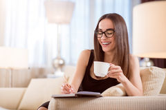 Woman drinking coffee and taking notes Royalty Free Stock Images