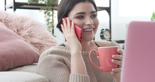 Woman drinking coffee and talking on phone. Beautiful woman drinking coffee and talking on mobile phone at home stock video footage