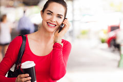 Woman drinking coffee and talking on phone. A beautiful woman out shopping holding a cup of coffee and talking on the phone stock photo