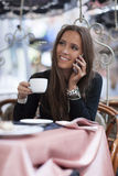 Woman drinking coffee and talking on the phone Royalty Free Stock Photo