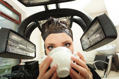 Woman drinking coffee tea in hair beauty salon. By hairdresser. Stock Photos