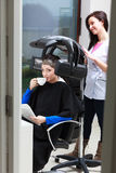 Woman drinking coffee tea in hair beauty salon. By hairdresser. Stock Image