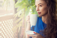 Woman drinking coffee at terrace Stock Image