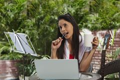 Woman drinking coffee, thinking and using a laptop Royalty Free Stock Photos