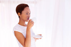 Woman drinking coffee. Thoughtful young african woman drinking coffee at home Stock Photo