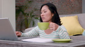 Woman drinking coffee while typing on laptop. At home stock video
