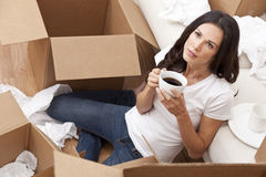 Woman Drinking Coffee Unpacking Boxes Moving House. A beautiful single young woman drinking tea or coffee unpacking boxes and moving into a new home royalty free stock photo