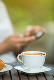 Woman drinking coffee and use smartphone Stock Images