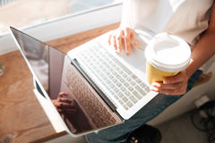 Woman drinking coffee and using blank screen laptop Royalty Free Stock Photo