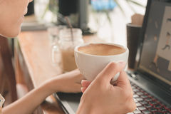 Woman drinking coffee and using computer. Stock Photos