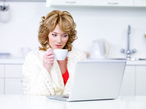 Woman drinking coffee and using laptop Royalty Free Stock Photos
