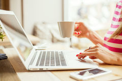 Woman drinking coffee and using laptop Stock Images