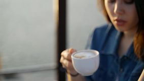 Woman drinking coffee while using laptop at cafe - close up. stock video