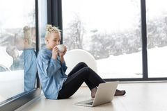 Woman drinking coffee and using laptop at home. Real Woman Using laptop on the floor Drinking Coffee Enjoying Relaxing at cold winter day Stock Image