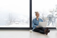 Woman drinking coffee and using laptop at home. Real Woman Using laptop on the floor Drinking Coffee Enjoying Relaxing at cold winter day Royalty Free Stock Photo