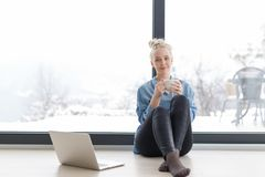 Woman drinking coffee and using laptop at home. Real Woman Using laptop on the floor Drinking Coffee Enjoying Relaxing at cold winter day Stock Photo
