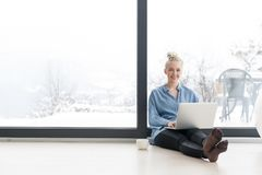 Woman drinking coffee and using laptop at home. Real Woman Using laptop on the floor Drinking Coffee Enjoying Relaxing at cold winter day Royalty Free Stock Image