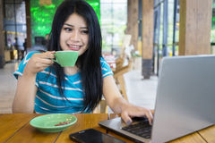 Woman drinking coffee while using laptop. Image of casual woman drinking coffee in the restaurant while using laptop computer on the table Royalty Free Stock Photography
