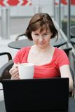 Woman drinking coffee and using laptop Stock Photos