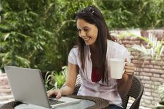 Woman drinking coffee and using a laptop Stock Photo