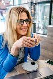 Woman drinking coffee and using the laptop. In a coffee shop Royalty Free Stock Photography