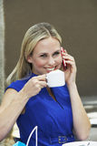 Woman Drinking Coffee While Using Mobile Phone Royalty Free Stock Photos