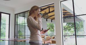 Woman drinking coffee and using mobile phone in kitchen at comfortable home 4k stock footage