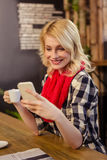 Woman drinking coffee and using smartphone Royalty Free Stock Photo