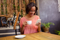 Woman drinking coffee and using smartphone Royalty Free Stock Photography