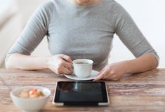 Woman drinking coffee and using tablet pc Stock Photos