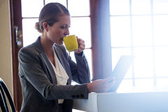 Woman drinking coffee and using tablet Royalty Free Stock Images