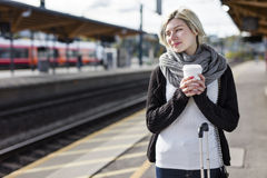 Woman drinking coffee while she waiting for the train Royalty Free Stock Photography