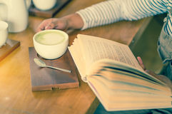 Woman drinking coffee. While reading book Stock Photos