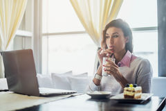 Woman drinking coffee working on laptop in cafe, morning breakfast stock images