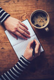 Woman drinking coffee and writing a diary note Stock Images