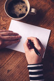 Woman drinking coffee and writing letters Royalty Free Stock Photography