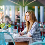 Woman drinking coffee and writing notes in cafe Stock Photography
