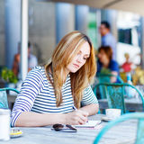 Woman drinking coffee and writing notes in cafe Royalty Free Stock Photos
